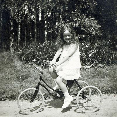 Marija Dymšaitė ant triračio Stončių dvaro parke