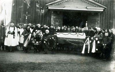 Laidotuvių dalyviai prie nežinomos bažnyčios Žemaitijoje