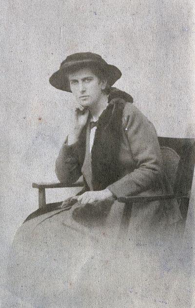 Jauna skrybėlėta aristokratė Kristina, sėdinti kėdėje