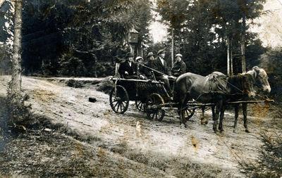 Grupė žmonių, važiuojančių miško keliu dvikinkiu vežimu
