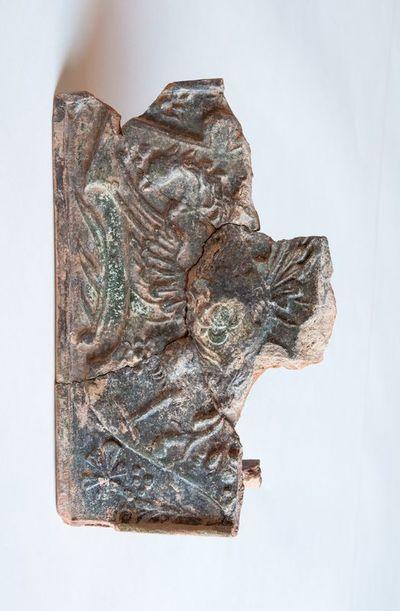 Dalinai išlikęs plokštinio koklio fragmentas
