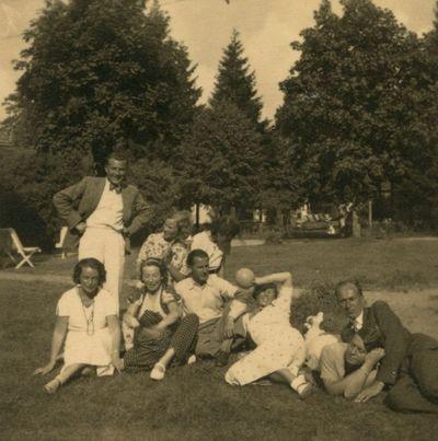 Poilsiautojai ant žolės prie vilos Palangoje
