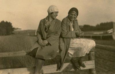 Gražutė Šlapelytė su drauge sėdi ant tvoros