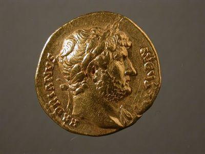 Anverso: Cabeça de Adriano, laureada, à direita. Inscrição: HADRIANVS.AVGVS[TVS] Reverso: Adriano com veste militar, levanta a mão direita e monta um cavalo em passo de trote, à direita. À volta: COS. III