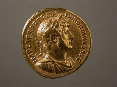 Anverso: Busto de Adriano laureado e drapeado, à direita. Inscrição: IMP. CAESAR.TRAIAN.HADRIANVS.AVG. Reverso: Júpiter, à esquerda, em tronco nú, sentado num trono, com pé em cima de uma base, segurando raio na mão direita e ceptro na esquerda. À volta: P.M.TR.P.COS.III.
