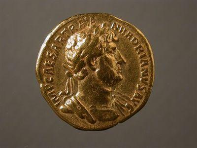 Anverso: Busto de Adriano laureado e drapeado, à direita. Inscrição: IMP. CAESAR.TRAIAN.HADRIANVS.AVG. Reverso: Hércules, de frente, sentando num rochedo, com maço na mão direita e pele sobre o rochedo. À volta: P.M.TR.P.COS.III.