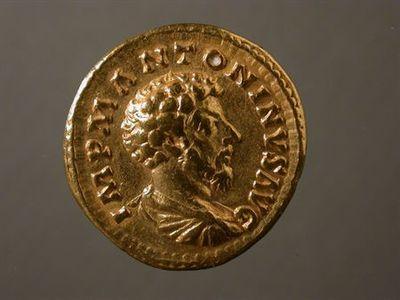 Anverso: Busto de Marco Aurélio, drapeado, à direita. À volta: IMP.M.ANTONINVS.AVG Reverso: Salus, à esquerda, drapeada, sacrificando pátera com a mão direita a um altar com serpente enrolada à volta. Na mão esquerda, segura um ceptro. À volta: SALVTI.AVGVSTOR.TR.P.XVII. No exergo: COS.III