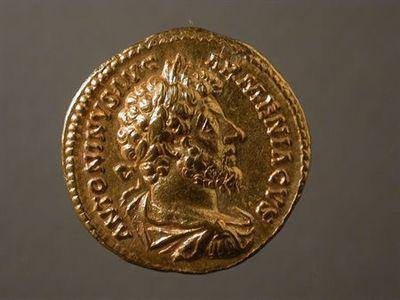 Anverso: Busto de Marco Aurélio, laureado, drapeado e couraçado, à direita. À volta: ANTONINVS.AVG.ARMENIACVS. Reverso: Vitória alada, nua até à cintura, virada à direita, com o pé esquerdo em cima de um capacete. Com a mão esquerda, segura um escudo com a inscrição : VIC / AVG, pousado numa palmeira. À volta: P.M.TR.P.XVIII.IMP.II.COS.III
