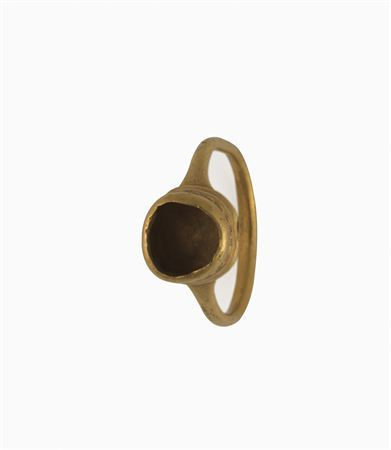Anel de aro circular, de secção circular, com engaste igualmente circular, para aplicação de uma pedra, inexistente. O engaste é decorado com uma faixa horizontal de pequenos quadrados obtidos através de punção.