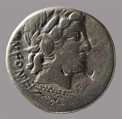 Anverso: Cabeça laureada de Apolo, à direita, em baixo três fiadas de pontos formam uma banda que por paralelos representariam um raio. Em baixo, à esquerda [M]N.FONTEI.[C.F.] Reverso: Cupido montado numa cabra, à direita, em cima dois pilae (chapéus). No exergo: um tirso. Toda a cena rodeada por coroa de louros.
