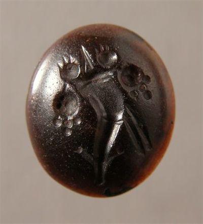 Pedra de anel de forma oval talhada e gravada na face superior. A gravação representa uma cornucópia.