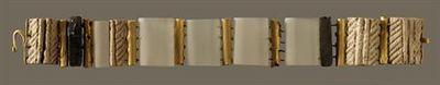 Bracelete aberto, constituído por elementos articulados dispostos paralelamente, formando uma banda rectangular. Três dos elementos são constituídos por placas rectangulares de osso com a face inferior plana e lisa e a superior convexa decorada por duas caneluras centrais, longitudinais, ladeadas por caneluras simétricas, paralelas e diagonais; um quarto elemento, originalmente idêntico está apenas representado por um fragmento correspondendo a metade da peça. Os restantes elementos, em ouro, co...