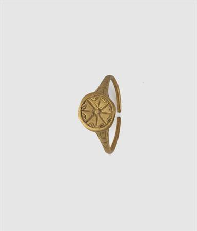 Anel de sinete, de ouro, com aro de secção circular que vai espessando progressivamente até formar uma mesa circular. Esta é decorada por uma flor estilizada de oito pétalas.
