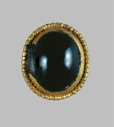 Adorno de ouro e granadas de forma oval. A parte interna é uma granada, rematada por um aro em ouro constituído por um arame retorcido.