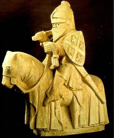 Escultura em calcário representando um cavaleiro vestido de guerreiro, com grande elmo, cota de malha, escudo de armas e espada, sapatos de bico e esporas. O cavalo está coberto com uma gualdrapa. O escudo tem as armas de Domingos Joanes: de azul, com aspa de prata acompanhada de quatro flores-de-lis de ouro.