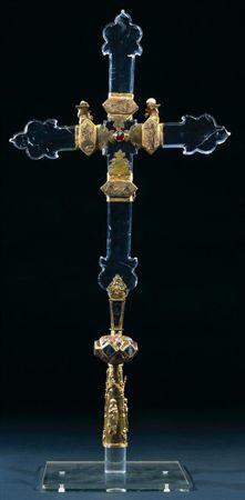 Cruz latina, de secção octogonal, em cristal de rocha. O pé cilíndrico-cónico e em prata dourada, tem representadas, repetidamente, duas imagens de Nossa Senhora e S. João sob arcaria gótica; pequenas figuras com uma cruz na mão sustentam as colunas da arcaria. Nó esférico hexagonal, de topos achatados, dividido em seis losangos, onde se inscrevem representações de santos com aplicações de esmalte translúcidos; folhas relevadas intercalam com os losangos. Estrutura de ligação à haste, de secção...