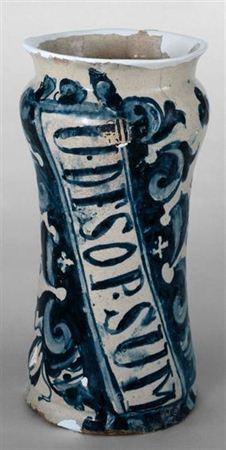 Canudo de faiança pintada a azul e branco que apresenta bordo subtilmente ressaltado e colo reentrante e curvilíneo. A peça bibojuda encontra-se decorada com reserva oblíqua, de duplo contorno, que possui a legenda U. DE.SO.SUM. O motivo decorativo possui moldura de volutas acantianas estilizadas, que percorrem dinamicamente a superfície de elemento morfológico, expandindo-se pelo colo e pela base sulcada profundamente.