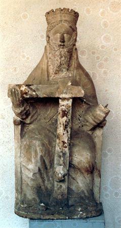 Escultura de vulto representando a Santíssima Trindade entronizada. O Criador coroado está sentado num trono escavado, apresentando cabelos curtos e ondulados. A face, de sugestão anatómica, ostenta barba longa, farta e ondulada. Traja manto que lhe cobre os ombros e parte do corpo, e túnica roçagante com pregas incisas. Seguraria entre as mão a cruz - actualmente em falta - com Cristo crucificado e encimada pela pomba (símbolo do Espírito Santo) . A escultura assenta sobre base circular de re...