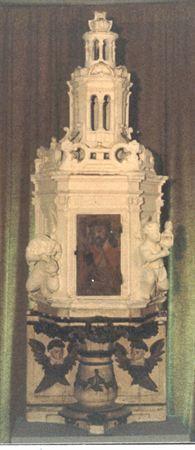 Sacrário pétreo, parcialmente dourado. Possui base com formato de vaso misulado, adossado a placa rectangular decorada com duas cabeças relevadas de anjos de asas douradas, uma de cada lado. O vaso é decorado com grinaldas volumosas, sendo a parte superior da mísula composta por friso de decoração vegetalista. Sacrário de micro-arquitectura renascentista, apresentando os vértices marcados por pilastras coríntias. A face principal possui uma porta de madeira pintada com a representação do Ecce Ho...