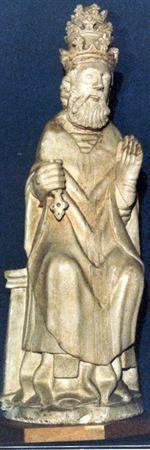 Escultura de calcário brando representando São Pedro entronizado. Possui tiara papal flordelizada sobre cabelos ondulados e curtos, face firme com olhos incisos e barba longa. O Santo de olhar alteado e paramentado, apresenta túnica roçagante com pregas incisas profundamente, estola sob dalmática e, a completar a indumentária de celebrante, casula com faixa vertical relevada, que possui pregas com formato de V. O santo, calçado, apresenta as mãos erguidas, segurando na dextra uma chave, seu atri...