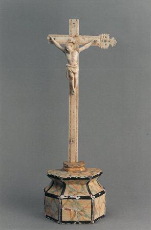 Escultura de marfim representando Cristo Crucificado e morto. Possui cabeça coroada de espinhos e inclinada para a direita, com cabelos longos e ondulados caindo pelas costas e face delicada e com barba. O corpo robusto e com sugestão anatómica, apresenta perisonium com pregas delicadas, caindo pelo lado direito até ao joelho. O Cristo encontra-se pregado, com o pé direito sobre o esquerdo, a uma cruz de marfim orlada com relevos, que apresenta em falta duas extremidades. O conjunto assenta sobr...