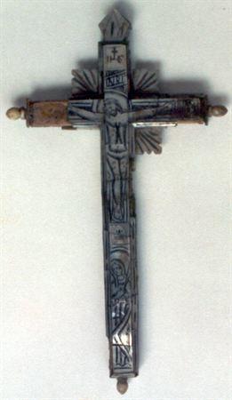 Crucifixo de dupla face, em madeira e revestido a madrepérola decorada com incisões. Possui, no braço vertical, um Cristo ensanguentado concretizado através de incisões suaves e policromia vermelha e preta. Três placas adossadas à cruz formam o resplendor do Salvador. As inscrições INRI e IHS, com crucifixo ao fundo, encimam o Cristo, encontrando-se colocadas em níveis diferentes. Uma mitra sob os pés do Cristo separa-o da Virgem orante e nimbada. Apresenta uma mitra a coroar o crucifixo, enquan...
