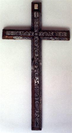 Crucifixo de pendurar, de arestas cortadas, formando três faces e revestido com madrepérola decorada com incisões pintadas a preto. Possui, no braço vertical superior, a incrição INRI encimada por um cálice, símbolo do sangue de Cristo, encontrando-se ladeado por uma igreja e uma cruz, colocadas nas faces laterais. No cruzamento dos quatro braços possui uma coroa de espinhos, simbolizando Cristo, que é o único caminho para a salvação. No braço vertical inferior, encontra-se a Virgem orante e n...