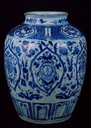 Pote de forma ovóide, ombros largos e colo curto com pequeno rebordo arredondado, executado no torno em porcelana branca, pesada e espessa. O corpo foi montado em duas partes, sendo a junção visível a meio do bojo. O vidrado, brilhante e ligeiramente azulado, cobre todo o corpo, à excepção da base que tomou uma cor alaranjada em contacto com a atmosfera do forno. A decoração, a azul cobalto intenso sob o vidrado, distribuída por três registos, separados entre si por dois círculos concêntricos, é...
