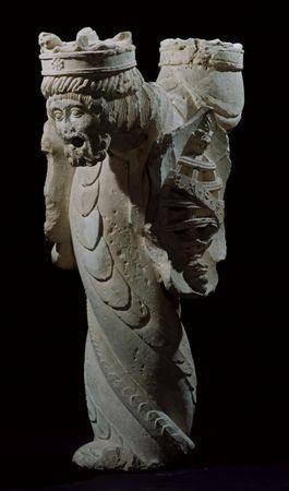 Fonte bicéfala composta por coluna torsa decorada com escamas de réptil, rematada por duas bicas antropomórficas, a da esquerda com rosto feminino coroado, e a da direita com rosto masculino barbado, com cabelos de madeixas estrigiladas, também coroado. Nas faces laterais da coluna relevam-se dois escudos. O primeiro, de recorte irregular, tem a esfera armilar esculpida em alto relevo, com meridiano onde corre inscrição marcada em baixo relevo E. M. P. R.. No segundo, com o mesmo recorte mostra...