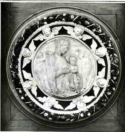 Medalhão em mármore com a representação da Virgem com o Menino acompanhados por dois putti trabalhados em baixo, médio e alto relevo. O medalhão é emoldurado por uma cercadura de duas secções demarcadas por círculos de óvulos e dardos. Na secção interna, côncava, de fundo azul, dispõe-se uma teoria de oito querubins de quatro asas (duas abertas e duas fechadas sob o rosto), aureolados. A secção externa desta cercadura é constituída por folhas, flores, pinhas, núcleos de opiáceas, que correm no...