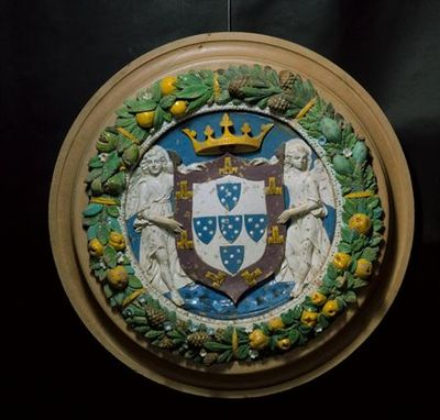 Medalhão em faiança policromada e esmaltada com a representação das armas reais portuguesas apresentadas por dois anjos tenentes esculpidos em baixo e médio relevo. O medalhão é emoldurado por cercadura de folhas (louro, pinheiro...), frutas (maçãs, romãs), pinhas e núcleos de opiáceas e flores que correm no sentido dos ponteiros do relógio em sete feixes contínuos demarcados por tiras amarelas. O lado interno da cercadura é constituído por um círculo de óvulos e dardos. No tondo, o escudo de...
