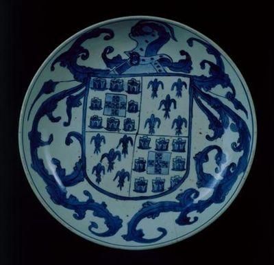 Prato fundo de porcelana branca de formato esférico rebaixado, com decoração a azul de cobalto. A qualidade da porcelana e da sua pintura apontam para uma manufactura cuidada e delicada. O azul foi directamente aplicado na porcelana antes da sua última cozedura.  O interior da peça é praticamente preenchido pela representação heráldica dos Albuquerque, em tonalidades de azul - escudo em chefe, esquartelado; com os I e IV campos, com as armas do Reino de Portugal (castelos e quinas) e os II e III...