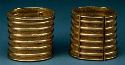 Pulseira em ouro, aro de perfil troncocónico com bordos de secção triangular, com extremidade boleada, decorados na parte externa com uma série de 49 (inf.) e 48 (sup.) triângulos isósceles com a base para o interior, incisos e preenchidos com reticulados, e seis toros equidistantes com os intervalos com três alinhamentos de espículas nos intervalos laterais e cinco alinhamentos nos restantes. Sistema de fecho por encaixe de um segmento móvel com quatro espigões de arame de secção circular intr...