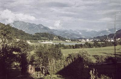[Vista de una localidad rural entre un río y las montañas con campos en primer plano]