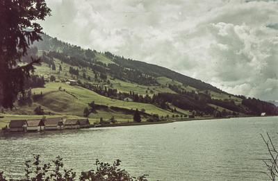 [Vista de lago con montañas al fondo y casas en la orilla]