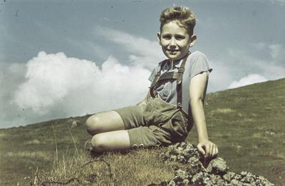 [Primer plano de Rodolfo, hijo del fotógrafo, sentado en unas rocas en la montaña]
