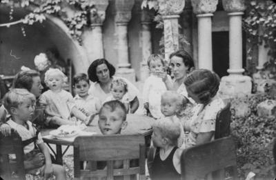 [Grupo de mujeres y niños sentados en una mesa en los jardines de la Embajada Alemana de Madrid esperando para ser evacuados tras el estallido de la Guerra Civil]