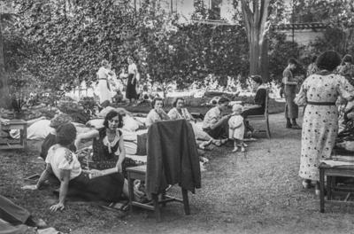 [Vista de personas sentadas en los jardines de la Embajada Alemana de Madrid refugiadas tras el estallido de la Guerra Civil]