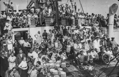 [Vista de personas congregadas en la cubierta del barco Baden que traslada a los refugiados a Alemania desde España tras el estallido de la Guerra Civil. Platos apilados para distribuir la comida]