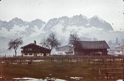 [Vista de casas de tejado a dos aguas en el bosque con montañas nevadas al fondo]