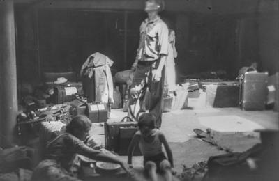 [Grupo de personas en la bodega del barco Baden, que traslada a evacuados alemanes desde España tras el estallido de la Guerra Civil: una mujer comiendo con un niño y personas tras ellos con sus maletas]