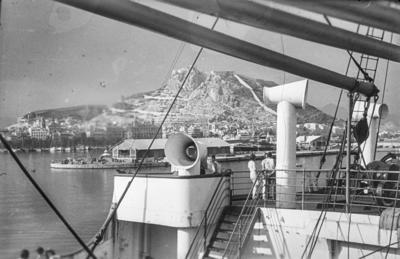 [Vista de personas en la cubierta superior del barco Baden que traslada a los alemanes evacuados desde España tras el estallido dela Guerra Civil. Puerto y montañas al fondo]