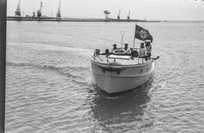 [Primer plano de marineros en una barca con bandera de cruz gamada]