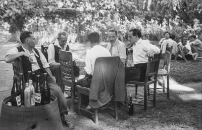 [Grupo de hombres sentados en torno a una silla jugando a las cartas junto a un tonel con bebidas en los jardines de la Embajada Alemana de Madrid refugiados tras el estallido de la Guerra Civil]