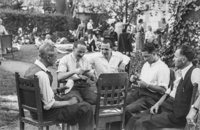 [Grupo de hombres sentados en torno a una silla jugando a las cartas en los jardines de la Embajada Alemana de Madrid refugiados tras el estallido de la Guerra Civil]