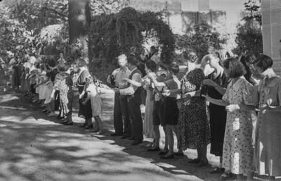[Grupo de personas formando una cadena con botellas de cristal en las manos para coger agua en los jardines de la Embajada Alemana de Madrid tras ser evacuados con el estallido de la Guerra Civil]