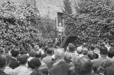 [Grupo de personas congregadas ante un hombre que lee un comunicado en las escaleras de los jardines de la Embajada Alemana de Madrid tras el estallido de la Guerra Civil]