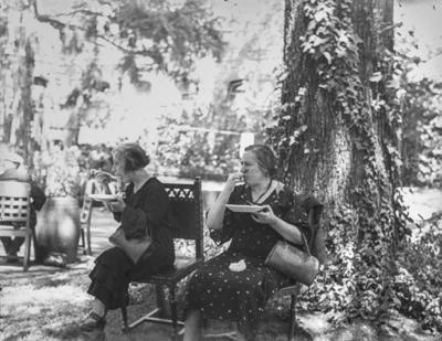 [Primer plano de dos personas comiendo sentadas a la sombra de un árbol un comunicado en las escaleras de los jardines de la Embajada Alemana de Madrid tras el estallido de la Guerra Civil]