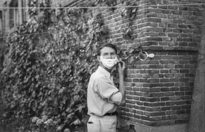 [Primer plano de un hombre afeitándose ayudándose de un espejo sujeto en la pared en los jardines de la Embajada Alemana de Madrid tras el estallido de la Guerra Civil]