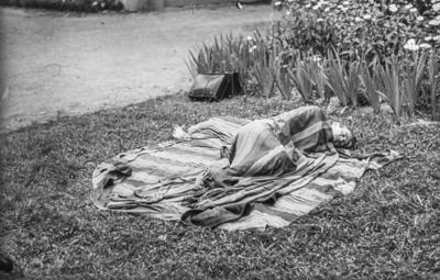 [Primer plano de persona durmiendo tapada con una manta en los jardines de la Embajada Alemana de Madrid tras el estallido de la Guerra Civil]